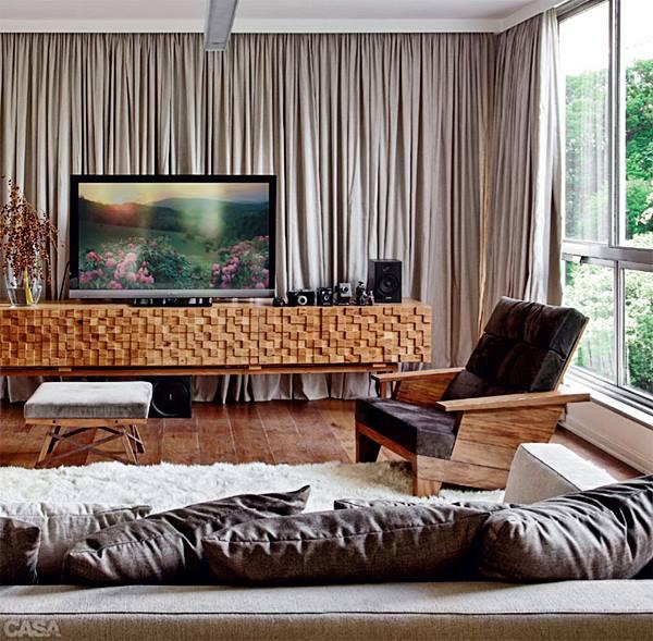 Tapete, madeira, texturas, almofadas, cortina. Esta sala deve ser ótima para ver um filme e o barulho não vai atrapalhar. É só fechar a janela e aproveitar. Até o móvel, com a madeira formando quadradinhos com diversas alturas é bom para melhorar o som na sala.